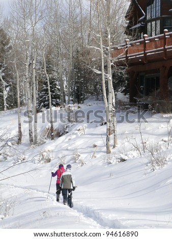 Snowshoers on winter trail near large modern homes inCordillera,Colorado