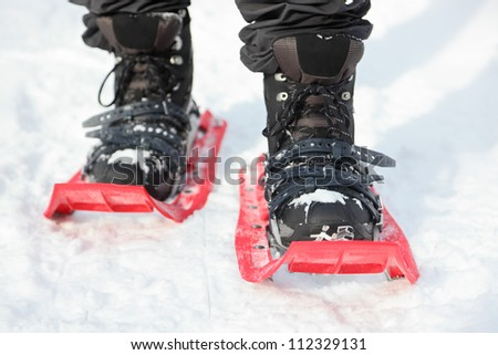 Snowshoes. Snowshoeing closeup. Red new modern high-end snowshoes. Man hiking in snow on snowy winter day.