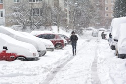 Snowstorm and snow-covered street and cars with a lonely pedestrian