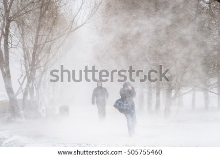 Snowstorm and strong wind in city Nothing visible Silhouettes of two men Blurred image