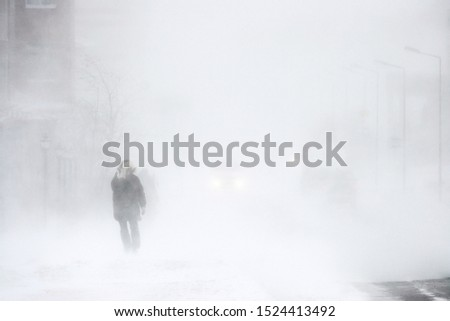Snowstorm in the city. A man during a blizzard is walking along the street. Cars on a snowy road. Strong wind and snowfall. Arctic climate. Extreme North. Anadyr, Chukotka, Siberia, Far East Russia. Foto stock ©