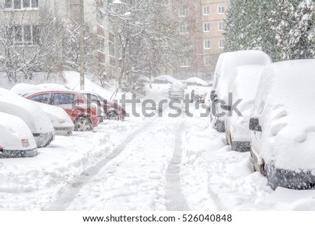 Snowstorm, snow-covered street and cars with a lonely pedestrian #526040848