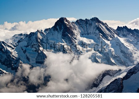 Snowy Alpen peaks above clouds - stock photo