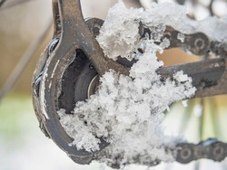 Snowy and dirty lubricated rear rail Derailleur. Detail of icy pulley of mountain bike gears with Spokes and snow in background