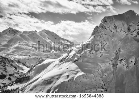 Snowy B&W mountain top with cloudy sky in the background Zdjęcia stock ©