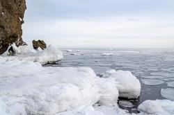 Snowy coast. Ice floes in the sea. Horizon. The frozen sea. Sakhalin island.