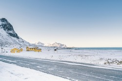 Snowy empty road along the sea & shoreline in the white cold world of north Norwegian islands. Yellow houses are lonely on the side of the street. Snow is full and so white under the clear blue sky.