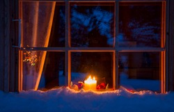 Snowy evening window of a wooden house. On the windowsill are Christmas decorations and burning candles