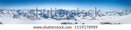 Snowy Greater Caucasus ridge with the Mt. Ushba at winter sunny day. Panoramic view from Pastuchova kliffs at Elbrus ski slope, Kabardino-Balkaria, Russia