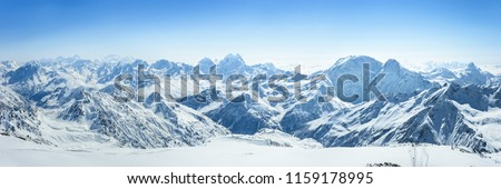 Snowy Greater Caucasus ridge with the Mt. Ushba at winter sunny day. View from Pastuchova kliffs at Elbrus ski slope, Kabardino-Balkaria, Russia #1159178995