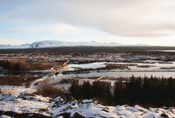 Snowy landscape of Thingvellir National Park in Iceland. Snow-capped mountains on the horizon and frozen landscape with lagoons and lava fields in Þingvellir.