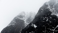Snowy mountain peaks, partially covered by mist and clouds in arctic Norway, Scandinavia.