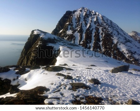 Snowy mountain pics under a clear blue sky and sea on the horizon. Brosmetinden, Kvaloya, Norway.