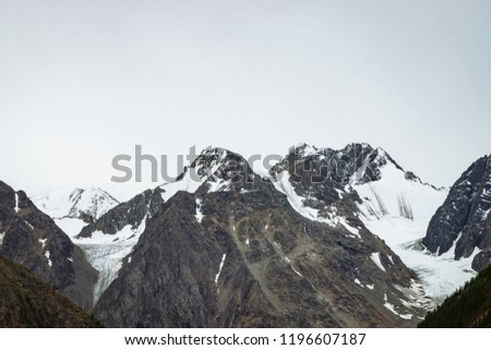 Snowy mountain top in blue clear sky. Rocky ridge under clouds in sunny day. Atmospheric minimalistic landscape of majestic nature.