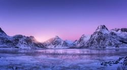 Snowy mountains, blue sea with frosty coast, reflection in water and purple sky at colorful sunset in Lofoten islands, Norway. Winter landscape with snow covered rocks, fjord with ice at night. Nature