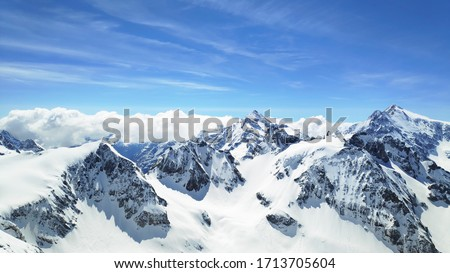 Snowy mountains covered in clouds beautified by the sky