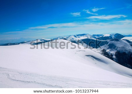 Snowy mountains on a sunny day. Mountain climbing and winter sports #1013237944
