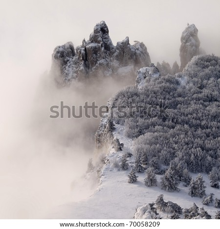 Snowy mountains with trees and fog.