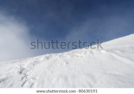 snowy mountainside  in fog and blue sky