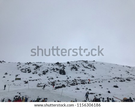 Snowy mountainside with skiers #1156306186