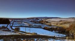 Snowy Nidderdale and late afternoon sun lights up moorland pastures, fields and a single track road