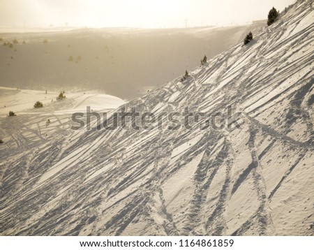 Snowy off-piste slope with rocks covered by tracks from snowboarder and skiers and other mountain slopes as background at sunrise, sunny cloudy winter weather (Andorra) #1164861859