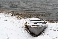 Snowy old rowing boat by the coast in winter season