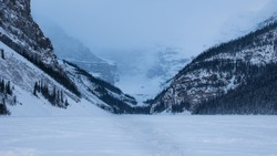 Snowy Path on a Frozen Lake in the Rocky Mountains and Glacier Mountain Peak in the Fog. Freezing Cold and Heavy Snowfall at Dusk. Majestic Mountain Range at Lake Louise