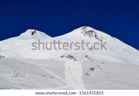 Snowy peaks of Elbrus, against a dark blue sky. The highest mountain peak in Russia and Europe. Photo taken on: November 2 Saturday, 2013