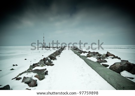 snowy pier in winter with tower