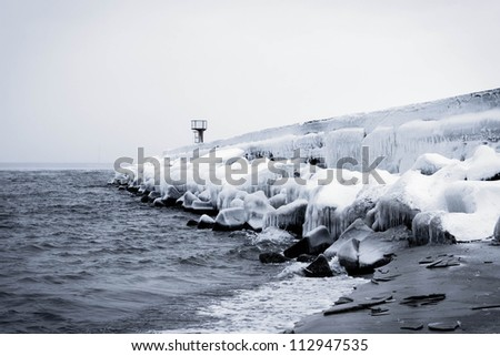 snowy pier in winter with tower in black and white - stock photo