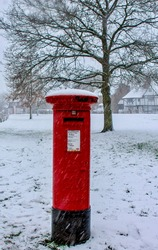 Snowy postbox on the village Green