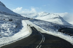 Snowy road with volcanic mountains in wintertime, Iceland