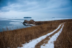 snowy rural road to the shore, dark cold winter landscape, beautiful dramatic background, road in snow through the field to the sea shore,