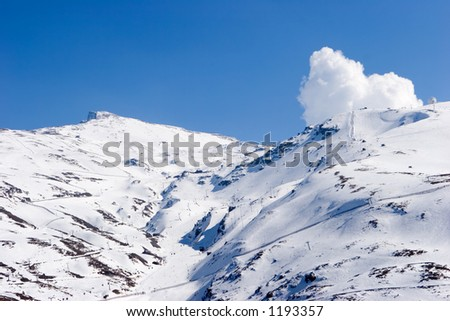 Snowy ski slopes of Pradollano ski resort in the Sierra Nevada mountains in Spain with people skiing and snowboarding