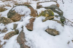 Snowy stones. Stones covered with snow. Stone.