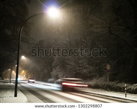 Snowy street with street lights at night,Car with motion blur driving on a snowy street with street lights at night, snowfall