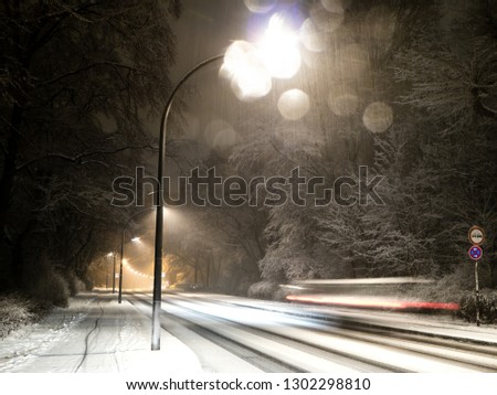 Snowy street with street lights at night,Car with motion blur driving on a snowy street with street lights at night, snowfall #1302298810
