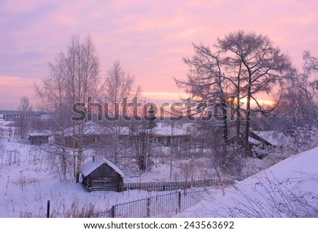 Snowy sunset landscape in winter dreamland in north Russia. Cold weather and a lot of snow. House in village. Warm colors filtered image.
