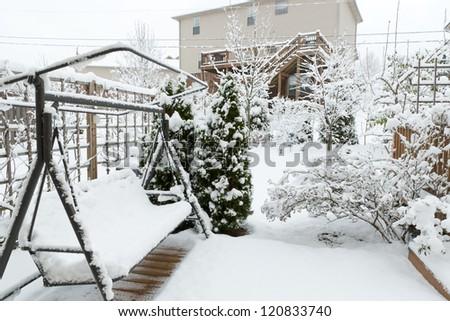 Snowy swing  on garden patio, winter scenery