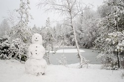 Snowy trees, snowman and frozen pond in winter