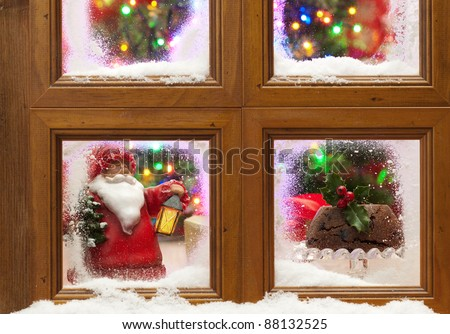 Snowy window with Christmas pudding and tree with twinkling fairy lights