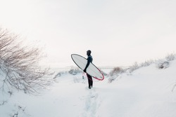 Snowy winter and surfer with surfboard. Winter beach and surfer in wetsuit.