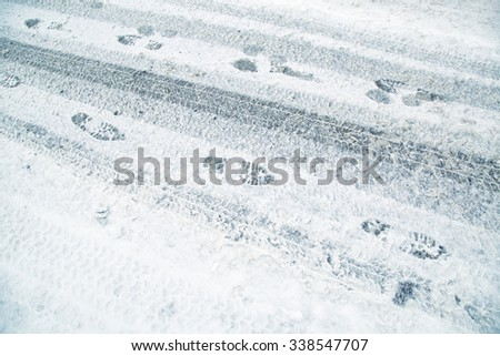 Snowy winter city asphalt road with tire trace and shoeprints. Danger icy and frozen city winter road background.
