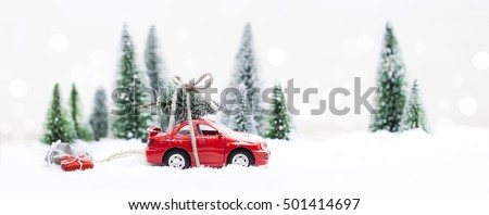 Snowy Winter Forest with miniature red car carrying a  christmas tree and presents Stok fotoğraf ©
