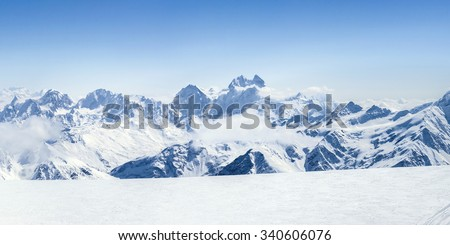 Snowy winter Greater Caucasus mountains (Ushba, Kogutai and other) at sunny day. Panorama view from ski slope Elbrus, Kabardino-Balkaria, Russia