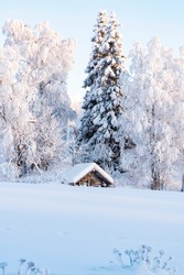 Snowy winter landscape of Lapland. Wooden, village houses covered with thick snow.