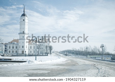 Snowy winter landscape with historical building of city hall of Mogilev, Belarus. Central city square on the embankment of river Dnepr