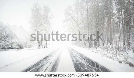 Snowy winter road during blizzard in Latvia #509487634