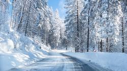 Snowy winter road in a mountain forest. Beautiful winter landscape.